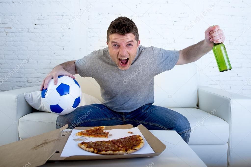 Young man holding ball watching football game on tv at home couch with  pizza and beer