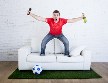 Football fan watching tv soccer celebrating goal in couch on grass carpet emulating stadium pitch