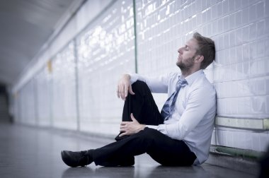 Young businessman lost in depression sitting on ground street subway