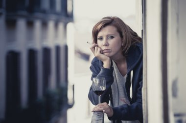 young woman suffering depression drinking wine outdoors at the balcony