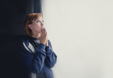 Attractive woman suffering depression saying a prayer to god for help