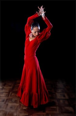 young Spanish woman dancing flamenco in traditional red dress