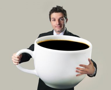 happy businessman holding funny huge  oversized cup of black cof