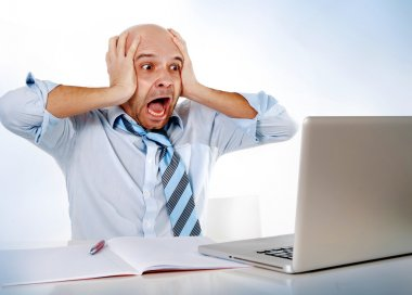 Hispanic overworked frustrated businessman on tie screaming in stress at computer laptop