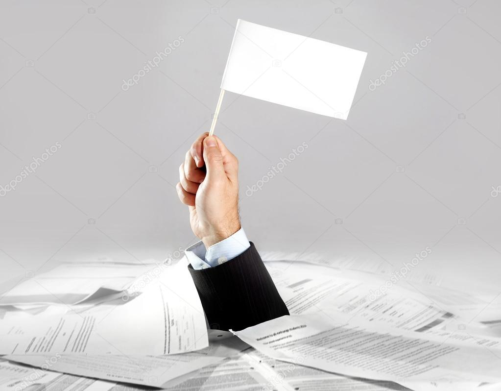 Hand of  businessman emerging from loaded paperwork desk holding white flag
