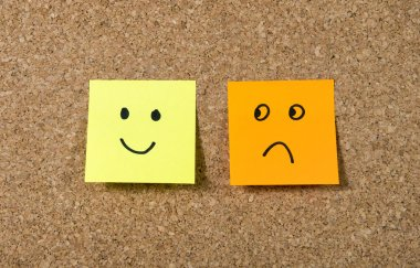 post it notes on corkboard with smiley and sad cartoon face expression in happiness versus depression concept