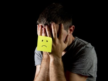 Young man suffering depression and stress alone with sad face post it note