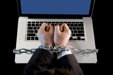 Hands of businessman addicted to work bond with chain to computer laptop in workaholic