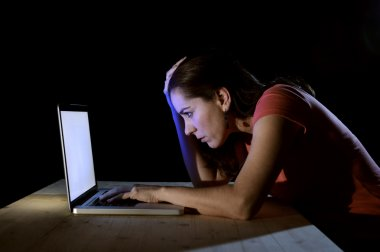 young concentrated freelance worker or student woman working with computer laptop alone late at night in stress studying for exam
