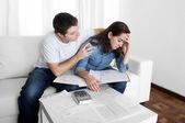 Mladý pár starosti doma v manžel stres uklidňující ženu ve finančních problémech