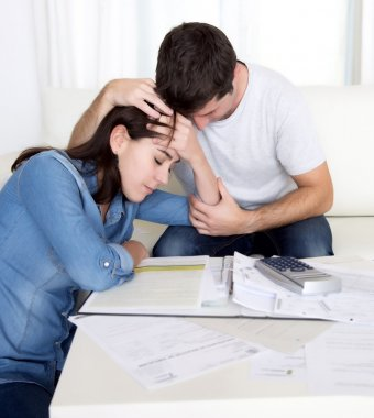 Young couple worried home in stress husband comforting wife in financial problems