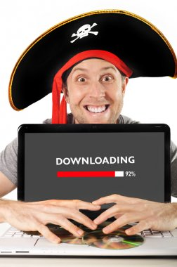Young man in pirate costume with Computer laptop downloading files copyright violation