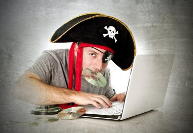 Man in pirate hat downloading music files and movies on computer laptop
