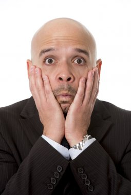 surprised Hispanic businessman in suit and tie looking scared, shocked and confused with hands on his face