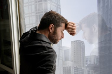 Attractive man leaning on business district window suffering emotional crisis and depression