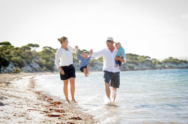 Young happy beautiful family walking together on the beach enjoying summer holidays