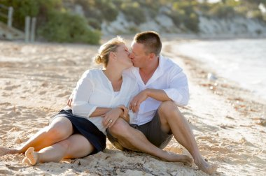 attractive beautiful  couple in love sitting on the beach in romantic summer holidays