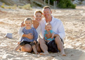 happy family couple sitting on beach sand with baby boy son and daughter
