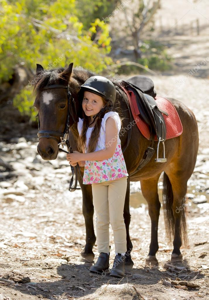 young girl 7 or 8 years old holding bridle of little pony horse smiling happy wearing safety jockey helmet in summer holiday