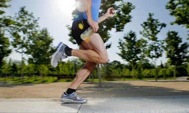 Close up athletic legs of young man running in city park with trees on summer training session practicing sport healthy lifestyle concept