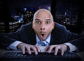 Fotografie businessman late at night in office typing on computer keyboard with funny face expression on watching porn online