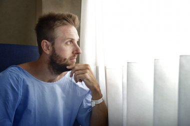 young injured man in hospital room sitting alone in pain worried for his health condition