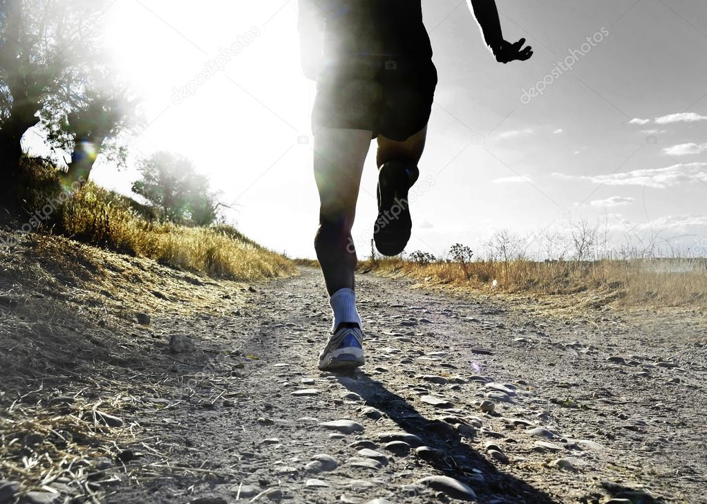 close up legs and feet of extreme cross country man running and training on rural track jogging at sunset