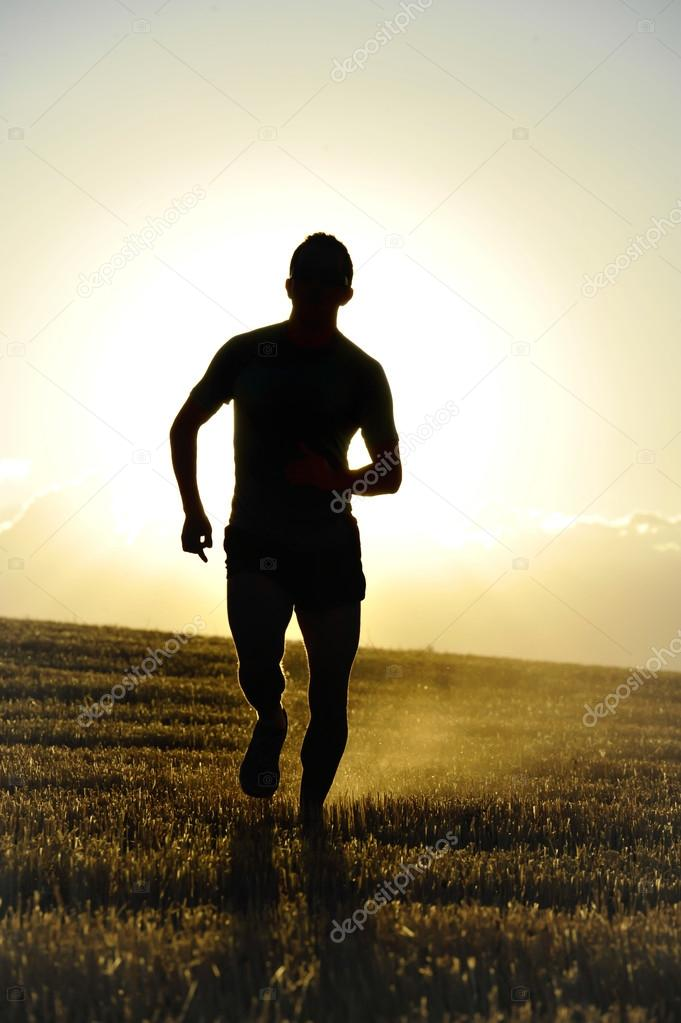 silhouette young sport man running off road in countryside straw field backlight at summer sunset