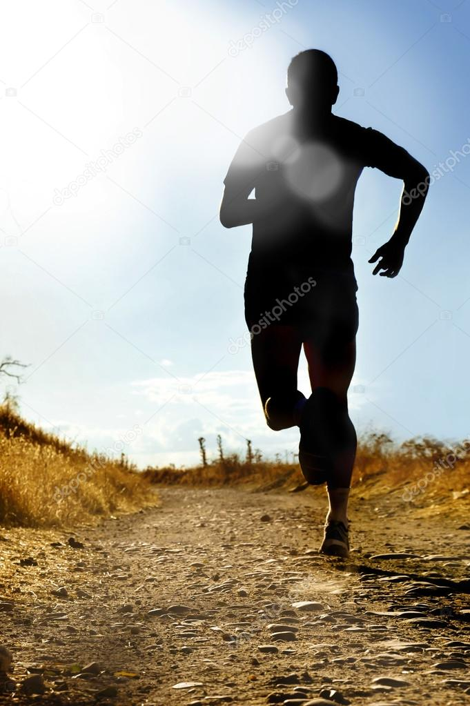 full body silhouette of extreme cross country man running on rural track jogging at sunset