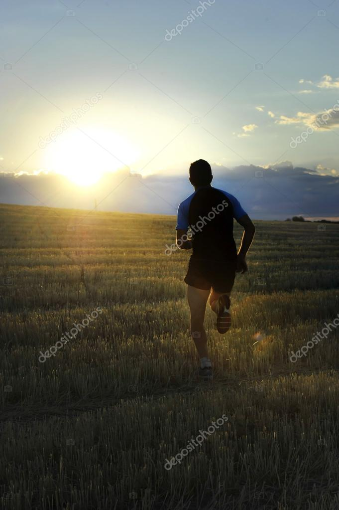 Silhouette sport man running off road in countryside on yellow grass field at sunset