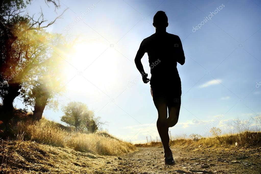 front silhouette young sport man running cross country workout at summer sunset