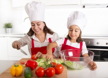 young mother and little daughter at house kitchen preparing salad for lunch wearing apron and cook hat