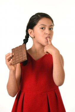 Hispanic female girl wearing red dress holding big chocolate bar eating in happy excited face expression licking her finger