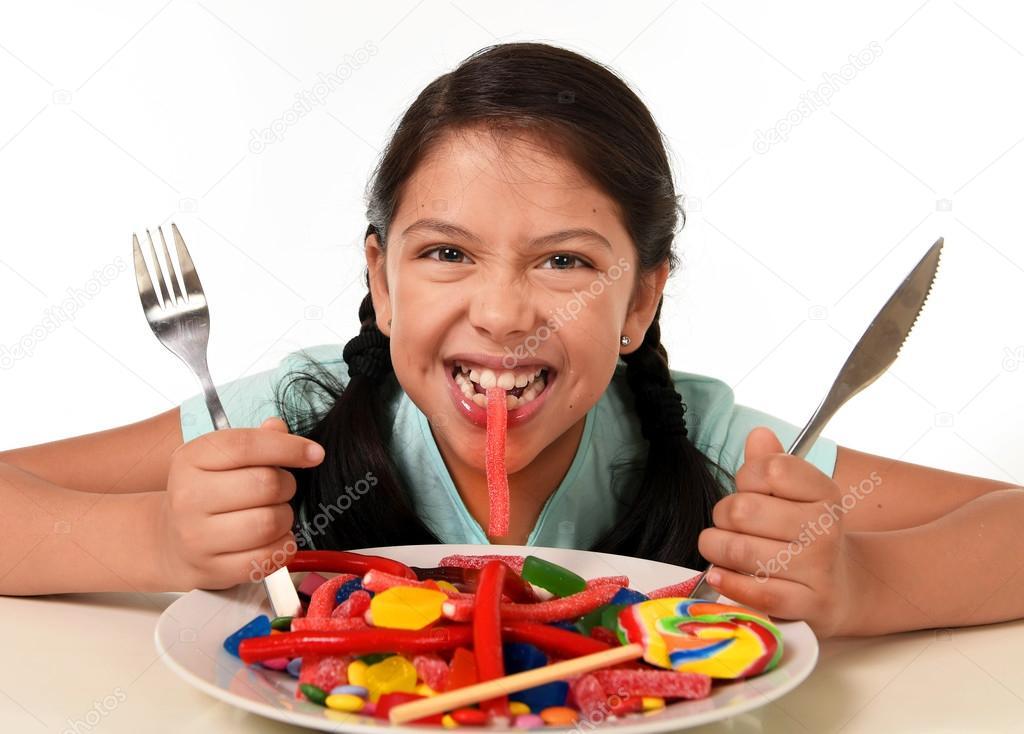 Ni o mujer latina emocionado feliz con tenedor y cuchillo for Tenedor y cuchillo en la mesa