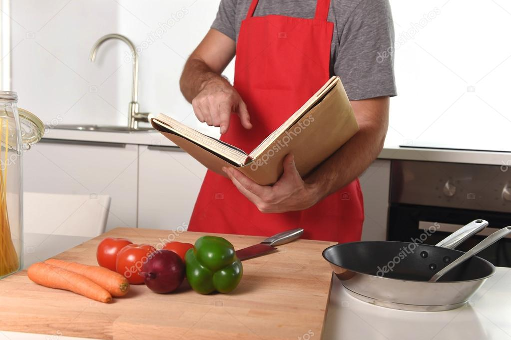 Unrecognizable man in apron at kitchen following recipe book hea unrecognizable man in apron at kitchen following recipe book hea fotos de stock forumfinder Image collections