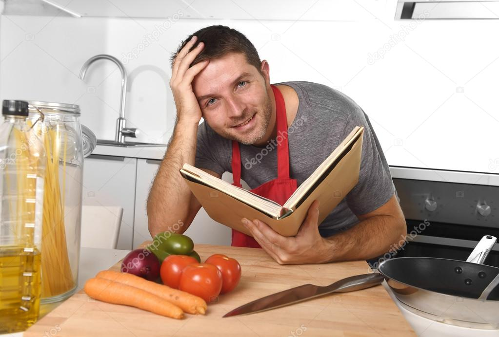 Young happy man at kitchen reading recipe book in apron learning young happy man at kitchen reading recipe book in apron learning foto de stock forumfinder Image collections