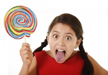 sweet beautiful latin female child holding big lollipop candy eating and licking happy and excited
