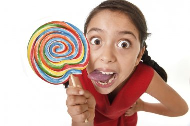 sugar addict latin female child holding big lollipop candy eating and licking happy crazy excited