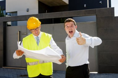 happy customer and constructor foreman worker talking on new house building blueprints in real state business concept