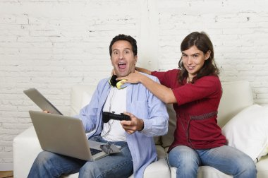 woman strangling technology freak husband or boyfriend for being electronic devices and internet addiction concept