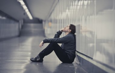 young sad woman in pain alone and depressed at urban subway tunn