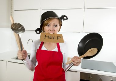 young attractive home cook woman in red apron at  kitchen holding pan and household with pot on her head in stress