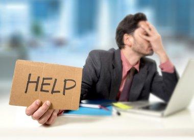 sad businessman at office desk working on computer laptop asking for help depressed