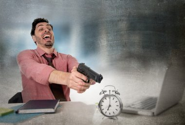 businessman in stress at office computer pointing hand gun to alarm clock project deadline expiring