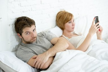 couple in bed husband frustrated upset and unsatisfied while his internet couple in bed husband frustrated upset unsatisfied while wife using mobile phone wife is using mobile phone