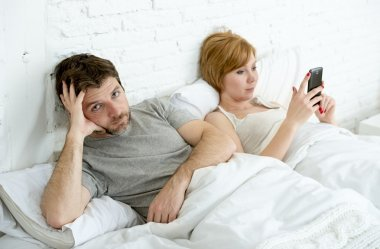 couple in bed husband frustrated upset unsatisfied while wife using mobile phone