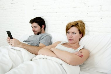 young couple in bed unsatisfied wife bored frustrated and angry while internet addict husband is using mobile phone  social network obsession