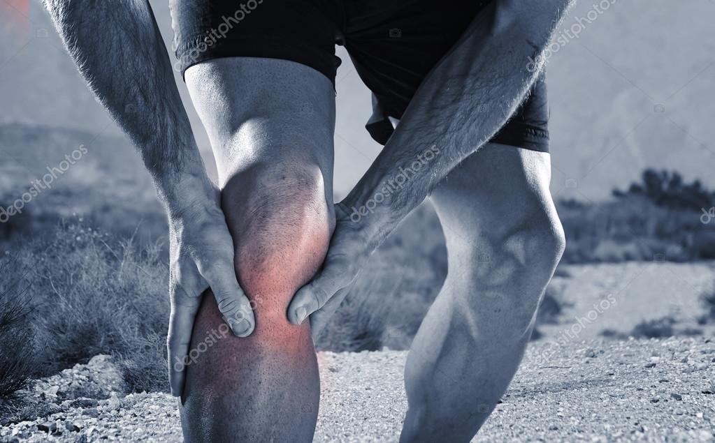 junge Sportler mit athletischen Beinen halten Knie Schmerzen leiden ...