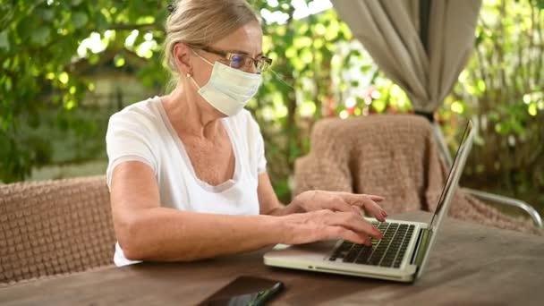 Technologie Altenpflege-Konzept - ältere Seniorin mit Mundschutz winkt im Videochat Laptop-Computer im Freien im Garten. Fernarbeit, Fernstudium. Virtuelles Ereignis Videokonferenz.