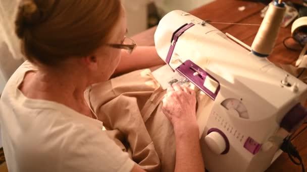 Sebevědomá starší žena švadlena bílá košile a brýle s šicím strojem, pracuje na oblečení doma pomocí béžové tkaniny. Osoby ve výslužbě, věk, koncepce zaměstnání